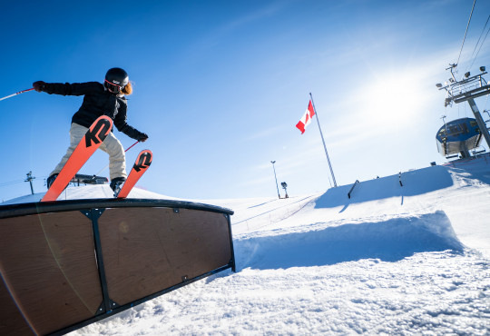Female skier at WinSport doing freestyle skiing trick on rail