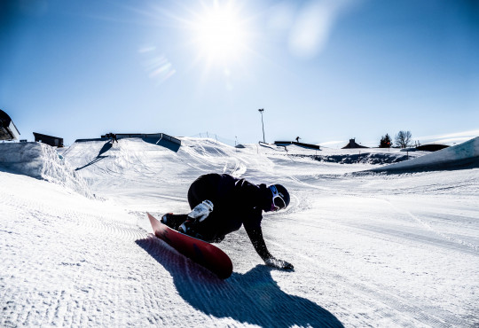 WinSport Snowboard intermediate snowboarder carves a turn and touches the snow with one hand