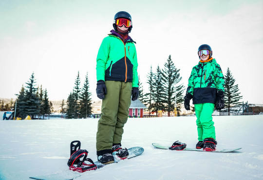 Winsport Snowboard teen boys wearing green snow suits posing with snowboards